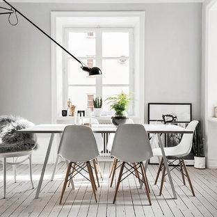 Idées déco pour une salle à manger scandinave de taille moyenne et fermée avec un mur blanc, un sol en bois peint et aucune cheminée.