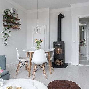 Bild på en skandinavisk matplats, med vita väggar, laminatgolv, en öppen vedspis och vitt golv