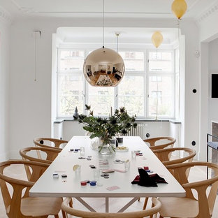 This is an example of a scandi dining room in Malmo with white walls.