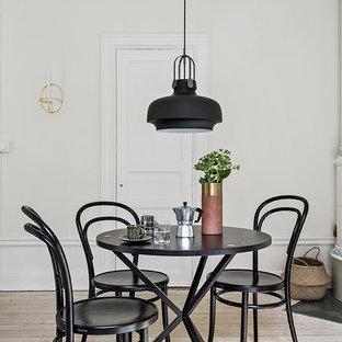 Nordisk inredning av en separat matplats, med vita väggar, ljust trägolv och beiget golv