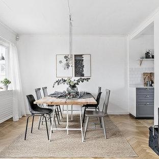 Idéer för en skandinavisk matplats, med vita väggar, ljust trägolv, en öppen vedspis och beiget golv