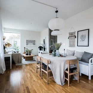 Inspiration för nordiska matplatser med öppen planlösning, med vita väggar, mellanmörkt trägolv och brunt golv