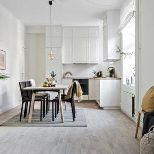 Nordisk inredning av en mellanstor matplats med öppen planlösning, med vita väggar och grått golv