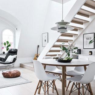 Exempel på en minimalistisk matplats med öppen planlösning, med vita väggar och beiget golv