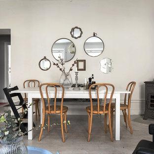 Inredning av en nordisk mellanstor matplats, med ljust trägolv, en öppen vedspis, en spiselkrans i metall, beige väggar och grått golv