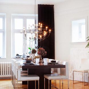 Réalisation d'une salle à manger minimaliste avec un mur blanc, un sol en bois brun et un sol orange.