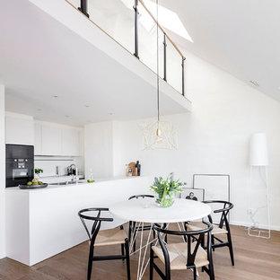 Foto på ett mellanstort minimalistiskt kök med matplats, med vita väggar och ljust trägolv