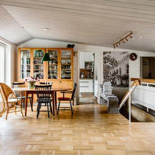 Minimalistisk inredning av en mellanstor matplats, med vita väggar, mellanmörkt trägolv och brunt golv