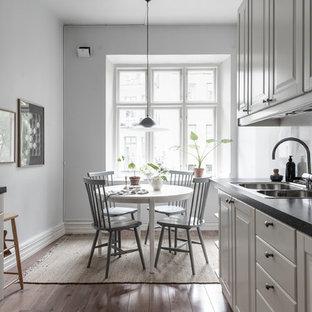 Bild på ett minimalistiskt kök med matplats, med grå väggar, mörkt trägolv och brunt golv
