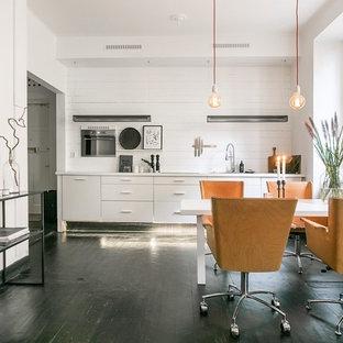 Idéer för att renovera en funkis matplats med öppen planlösning, med vita väggar, målat trägolv och svart golv