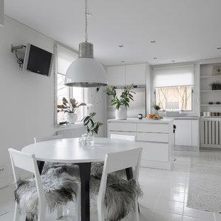 Inredning av ett minimalistiskt mellanstort kök med matplats, med vita väggar och vitt golv