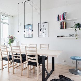 Minimalistisk inredning av en mellanstor matplats, med vita väggar, ljust trägolv och beiget golv