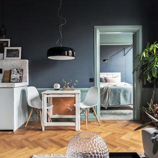 Immagine di una piccola sala da pranzo aperta verso la cucina scandinava con pavimento in legno massello medio, nessun camino e pareti nere