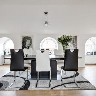 Modern inredning av en stor matplats med öppen planlösning, med vita väggar, ljust trägolv och beiget golv
