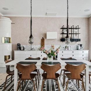 Ispirazione per una sala da pranzo aperta verso la cucina nordica di medie dimensioni con parquet chiaro, pavimento beige, pareti rosa e camino ad angolo