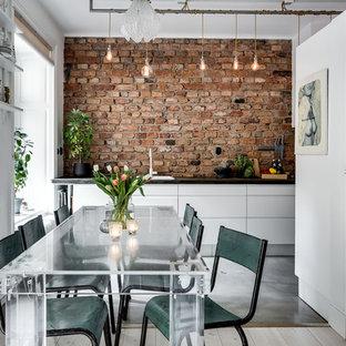 Immagine di una grande sala da pranzo aperta verso la cucina scandinava con pareti bianche e pavimento in cemento