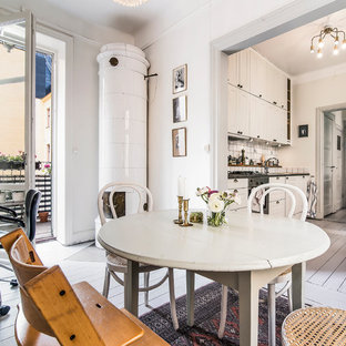 Mid-sized danish painted wood floor kitchen/dining room combo photo in Stockholm with white walls and a wood stove