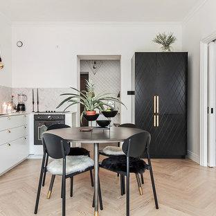 Cette image montre une salle à manger ouverte sur le salon nordique de taille moyenne avec un mur blanc, un sol en bois clair et aucune cheminée.