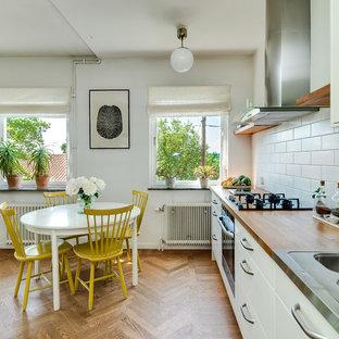 Idéer för ett mellanstort minimalistiskt kök med matplats, med vita väggar och ljust trägolv