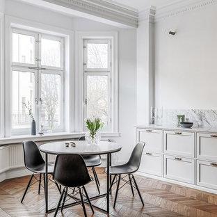 Inredning av ett nordiskt stort kök med matplats, med mellanmörkt trägolv, vita väggar och brunt golv