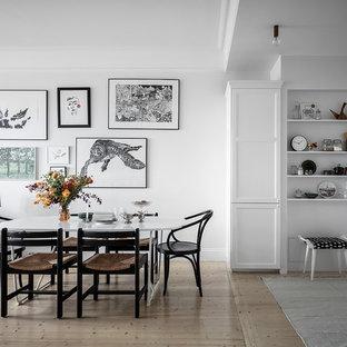 Foto på en skandinavisk matplats med öppen planlösning, med vita väggar, ljust trägolv och beiget golv