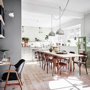 Foto på en stor minimalistisk matplats med öppen planlösning, med gröna väggar och ljust trägolv
