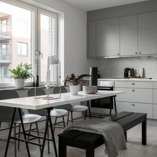 Foto på ett minimalistiskt kök med matplats, med vita väggar, ljust trägolv och beiget golv