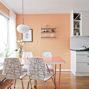 Cette image montre une salle à manger ouverte sur la cuisine nordique avec un mur orange, un sol en bois brun et un sol marron.