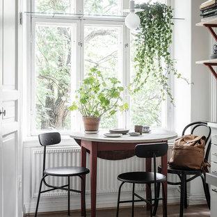 Bild på ett skandinaviskt kök med matplats, med vita väggar, mörkt trägolv och brunt golv