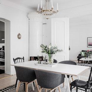 Inredning av en minimalistisk separat matplats, med vita väggar, ljust trägolv, en öppen hörnspis och beiget golv