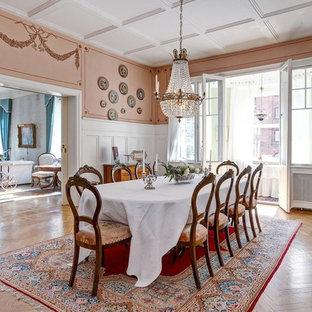 Réalisation d'une grande salle à manger tradition fermée avec un mur rose, un sol en bois brun et aucune cheminée.