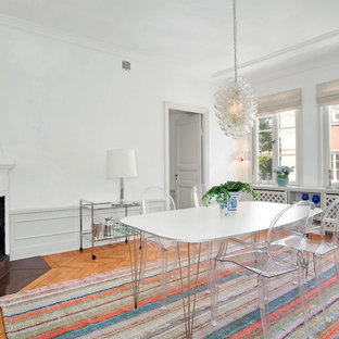 Example of a large danish medium tone wood floor enclosed dining room design in Stockholm with white walls and a corner fireplace