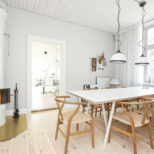 Design ideas for a mid-sized scandinavian dining room in Stockholm with white walls, light hardwood floors, a wood stove and beige floor.