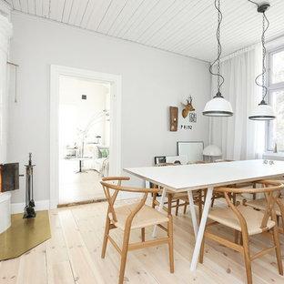 Inredning av en nordisk mellanstor matplats, med vita väggar, ljust trägolv, en öppen vedspis och beiget golv