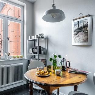 Idéer för att renovera ett litet minimalistiskt kök med matplats, med grå väggar och svart golv