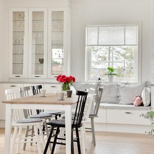 Idéer för mellanstora lantliga matplatser med öppen planlösning, med vita väggar och ljust trägolv
