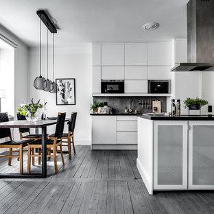 Inredning av en skandinavisk mellanstor matplats, med vita väggar, mörkt trägolv och grått golv
