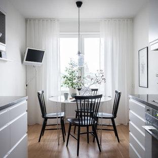 Idéer för minimalistiska matplatser, med vita väggar, mellanmörkt trägolv och beiget golv