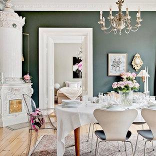 Inredning av en minimalistisk matplats, med gröna väggar, ljust trägolv, en öppen hörnspis och beiget golv