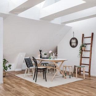 Bild på en stor skandinavisk matplats med öppen planlösning, med vita väggar, mellanmörkt trägolv och brunt golv