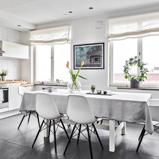 Kitchen/dining room combo - mid-sized scandinavian slate floor and gray floor kitchen/dining room combo idea in Gothenburg with white walls