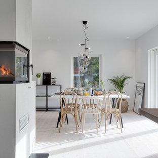 Foto di una sala da pranzo scandinava con pareti bianche, pavimento in legno verniciato, pavimento bianco, camino ad angolo e cornice del camino in metallo