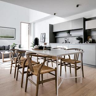 Minimalistisk inredning av ett mellanstort kök med matplats, med vita väggar, beiget golv och ljust trägolv