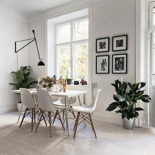 Idée de décoration pour une salle à manger ouverte sur le salon nordique de taille moyenne avec un mur blanc, un sol en bois peint et aucune cheminée.