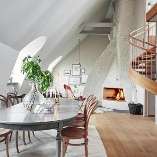 Foto de comedor ecléctico, grande, abierto, con suelo de madera clara, paredes blancas, chimenea de esquina y marco de chimenea de yeso
