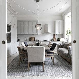 Foto på ett stort minimalistiskt kök med matplats, med vita väggar, ljust trägolv och beiget golv