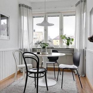 Nordisk inredning av en liten matplats, med vita väggar, mellanmörkt trägolv och beiget golv