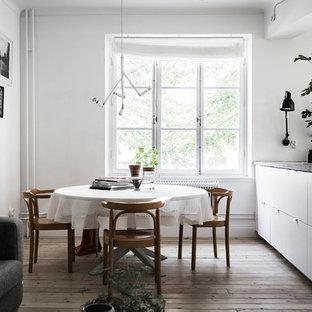 Idéer för att renovera en mellanstor minimalistisk matplats med öppen planlösning, med vita väggar, ljust trägolv och beiget golv