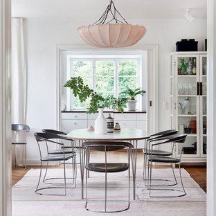 Idéer för att renovera en mellanstor funkis separat matplats, med vita väggar och mellanmörkt trägolv