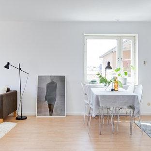 Skandinavisk inredning av en matplats med öppen planlösning, med vita väggar, ljust trägolv och beiget golv
